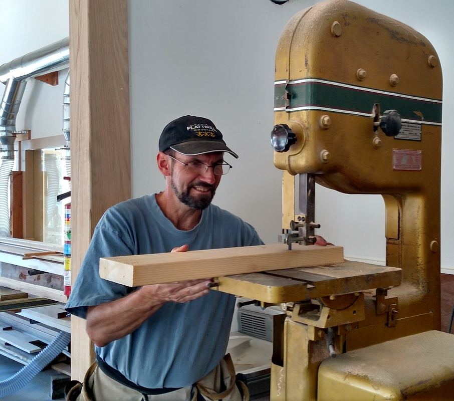 Riverport Youthboat Instructor Wayne Ford uses machinery to cut wood.